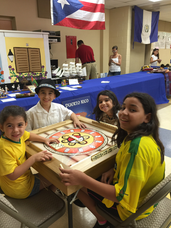 Kids at an Orlando elementary school play dominoes during their Multicultural Festival. The educational, social, psychological and health benefits of playing table games is well documented by numerous studies.